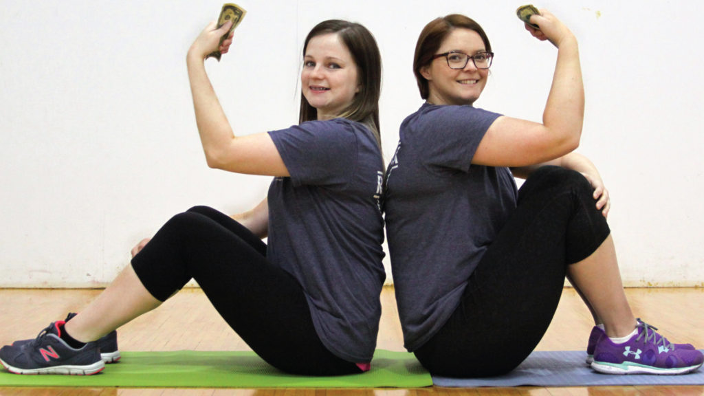 Ladies holding money on yoga mats
