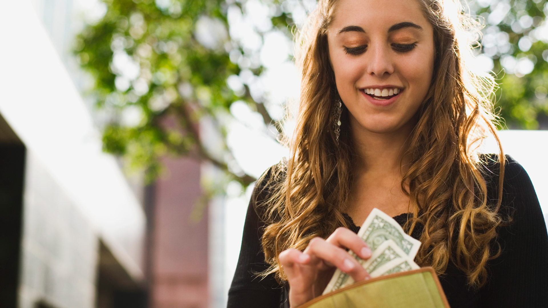 Teen girl removing money from wallet