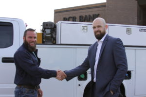 business owner Jesse Jones shaking hands with market president Garrett Chaney